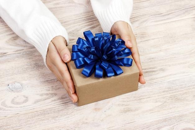 Jonge vrouwenhanden die giftdoos met blauw lint houden