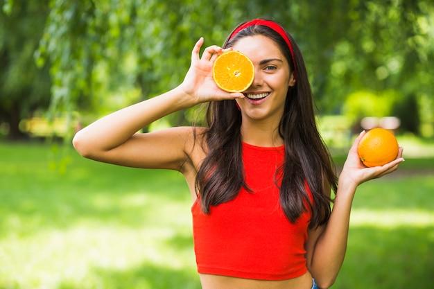 Jonge vrouwenholding gehalveerde sinaasappel voor haar oog