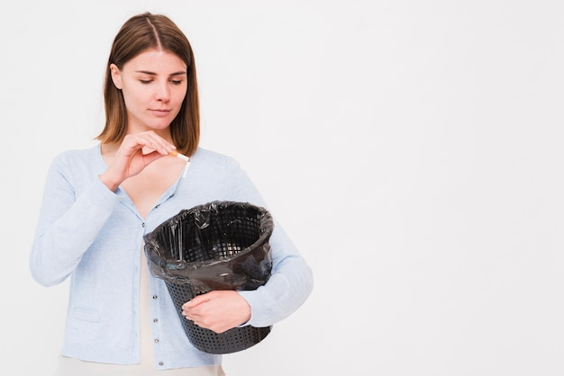 Jonge vrouwenholding vuilnisbak en het werpen van sigaret
