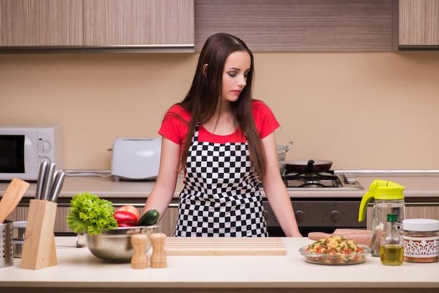 Jonge vrouwenhuisvrouw die in de keuken werkt