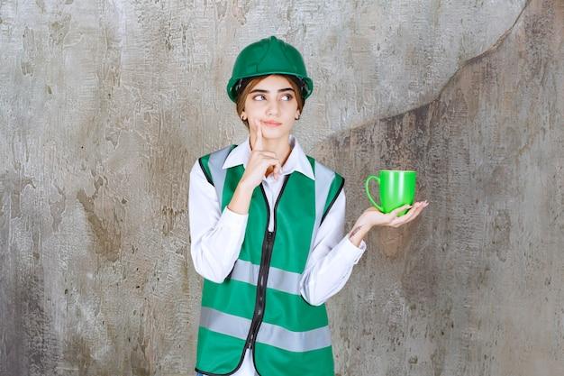 Jonge vrouweningenieur die een groen vest draagt en een koffiekop houdt