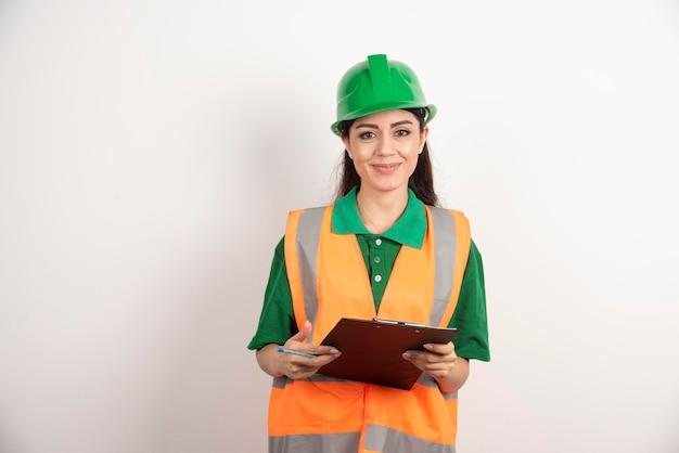 Jonge vrouweningenieur die een klembord met glimlach houdt. hoge kwaliteit foto