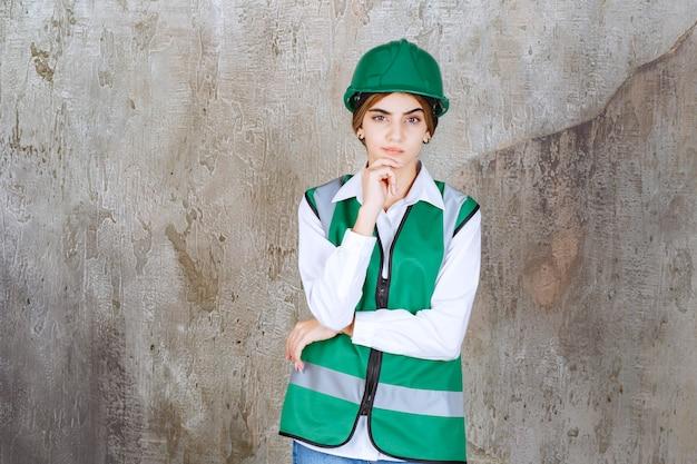 Jonge vrouweningenieur in groen vest en helm die camera bekijken