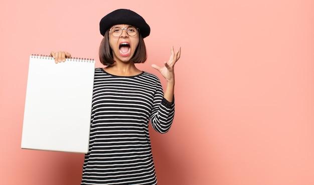 Jonge vrouwenkunstenaar die met handen in de lucht gilt, zich woedend, gefrustreerd, gestrest en boos voelt