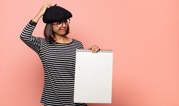 Jonge vrouwenkunstenaar die zich in verwarring en verward voelen, hoofd krabben en naar de kant kijken