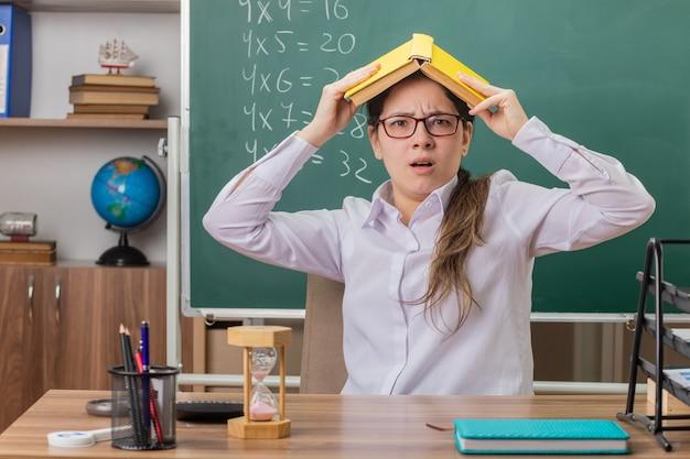 Jonge vrouwenleraar die glazen draagt die boek over haar hoofd houden die moe en geïrriteerd zittend aan schoolbank voor bord in klaslokaal kijken