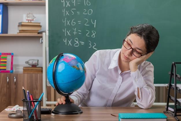 Jonge vrouwenleraar die glazen draagt die bol houdt die het bekijkt wordt moe