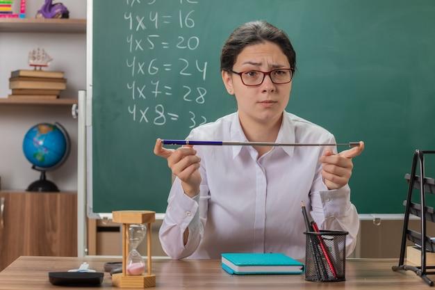 Jonge vrouwenleraar die glazen draagt die voorzijde met ernstig gezicht bekijkt die aanwijzer gaat uitleggen les zit aan schoolbank voor schoolbord in klas