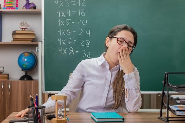 Jonge vrouwenleraar die glazen met zandloper en notitieboekje draagt