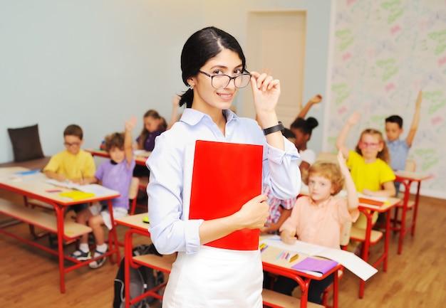 Jonge vrouwenleraar met glazen, studenten op basisschool. terug naar school