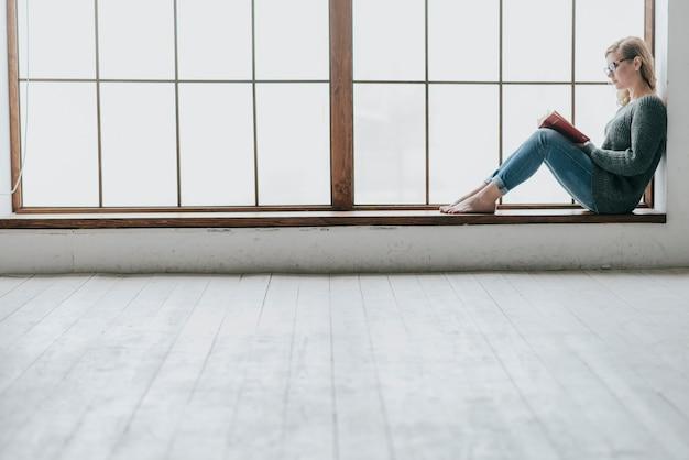 Jonge vrouwenlezing dichtbij reusachtig venster