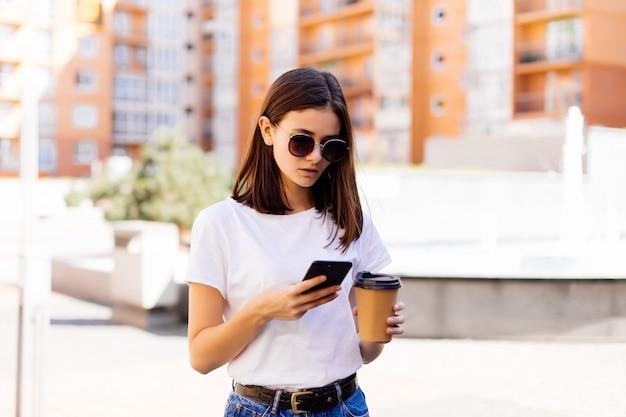 Jonge vrouwenlezing die telefoon met behulp van. het vrouwelijke nieuws van de vrouwenlezing of het sms'en van sms op smartphone terwijl het drinken van koffie op onderbreking van het werk.