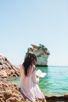 Jonge vrouwenlezing op tropisch wit strand