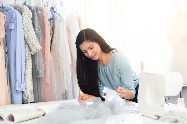 Jonge vrouwennaaister die kleren op calqueerpapier met patroon ontwerpen