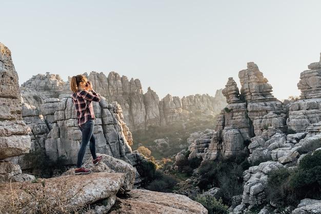Jonge vrouwenontdekkingsreiziger die in de berg fotograferen. concept van avontuur, excursies en uitstapjes.