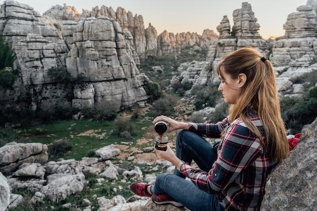 Jonge vrouwenontdekkingsreiziger die koffie in een kop op de berg maken. concept van avontuur, excursies en uitstapjes.
