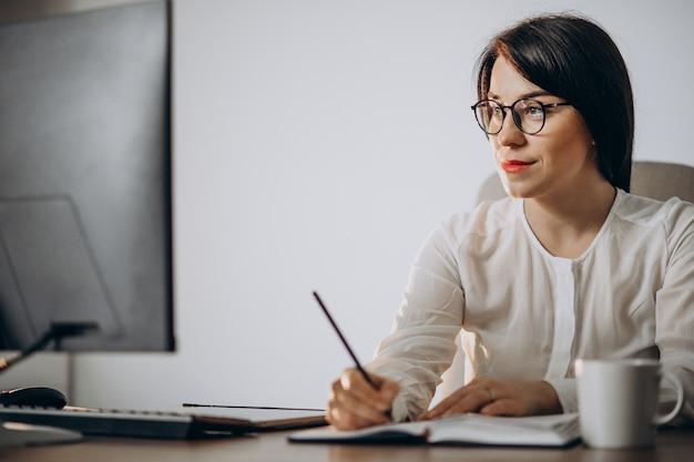 Jonge vrouwenontwerper die bij het bureau werkt