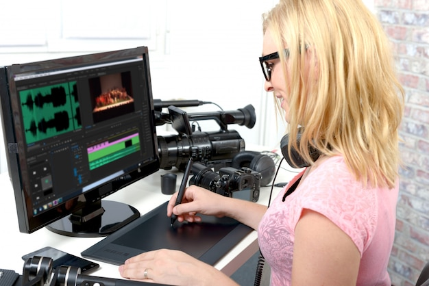 Jonge vrouwenontwerper die computer voor videobewerking met behulp van