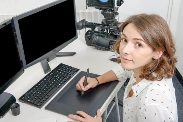 Jonge vrouwenontwerper die grafisch tablet gebruiken