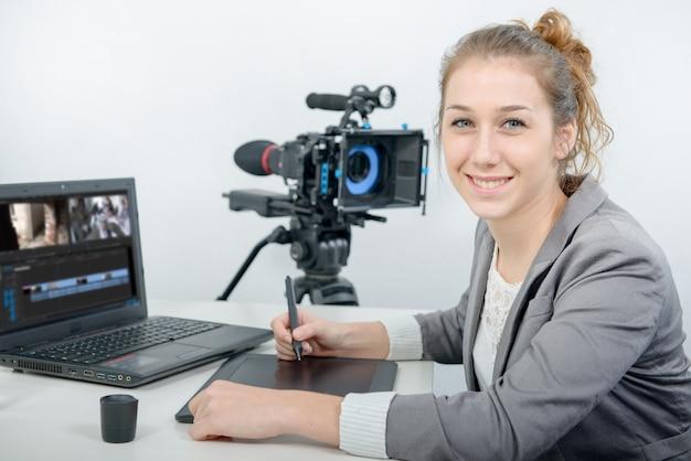Jonge vrouwenontwerper die grafisch tablet voor videobewerking gebruiken