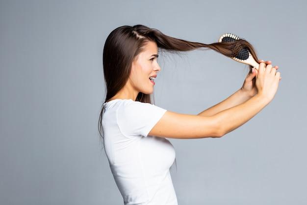 Jonge vrouwenproblemen met haar, gespleten zwak haar, verward haar dat op grijs wordt geïsoleerd