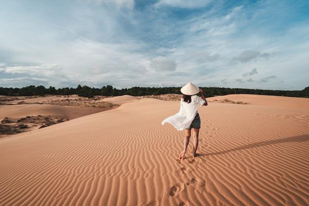 Jonge vrouwenreiziger die bij rode zandduinen lopen in vietnam, het concept van de reislevensstijl