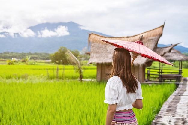 Jonge vrouwenreiziger die en met mooi groen padiegebied kijken ontspannen