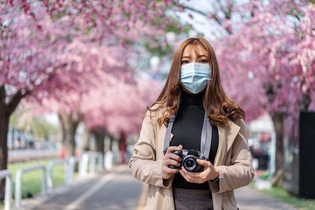 Jonge vrouwenreiziger die gezichtsmasker dragen en kersenbloesems of sakurabloem kijken die in het park bloeien