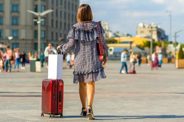 Jonge vrouwenreiziger die haar karretje rode zak op de straat dragen