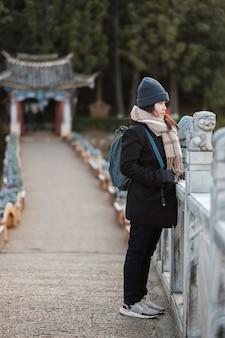 Jonge vrouwenreiziger die in black dragon pool met jade dragon snow mountain, oriëntatiepunt en populaire vlek voor toeristenaantrekkelijkheden dichtbij de oude stad van lijiang reizen. lijiang, yunnan, china
