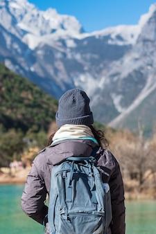 Jonge vrouwenreiziger die in blue moon valley, oriëntatiepunt en populaire vlek binnen het jade dragon snow mountain scenic area, dichtbij de oude stad van lijiang reizen. lijiang, yunnan, china. solo reisconcept