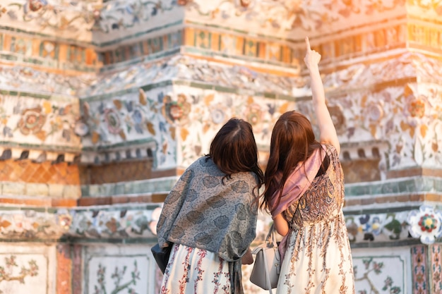 Jonge vrouwenreiziger die in wat arun ratchawararam ratchawaramahawihan-tempel in bangkok reizen