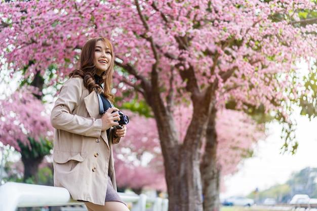 Jonge vrouwenreiziger die kersenbloesems of sakurabloem kijken die en camera bloeien om een foto in het park te nemen