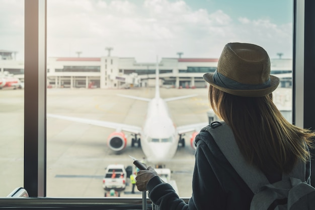 Jonge vrouwenreiziger die met het paspoort van de bagageholding airplan bekijken