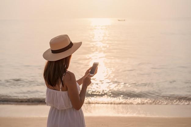 Jonge vrouwenreiziger die mobiele telefoon op tropisch strand gebruiken bij zonsondergang, vakantie en de zomerconcept