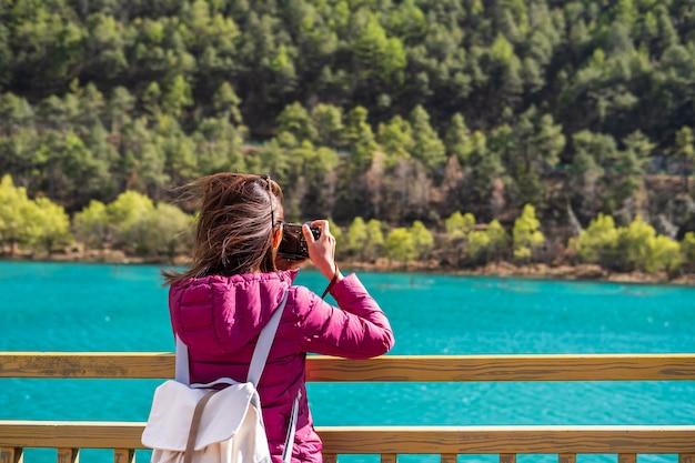 Jonge vrouwenreiziger die mooie aard blauwe maannvallei in china, het concept van de reislevensstijl bekijken
