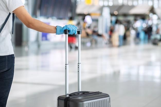 Jonge vrouwenreiziger die nitrilhandschoen draagt ?? die handvatbagage in luchthaventerminal houdt, bescherming coronavirus-infectie (covid-19). nieuw normaal en reisballonconcept