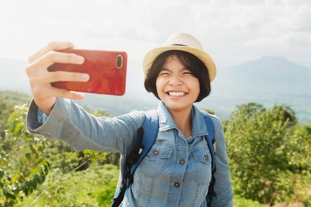 Jonge vrouwenreiziger die selfie met bergmening nemen