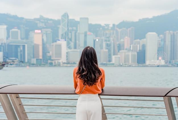 Jonge vrouwenreiziger die van bij hong kong-cityscape de stad in over victoria harbor genieten
