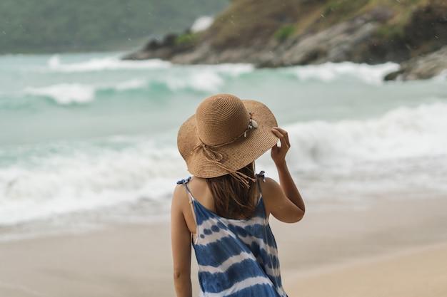 Jonge vrouwenreiziger die zich alleen bij het strand op winderige dag bevindt