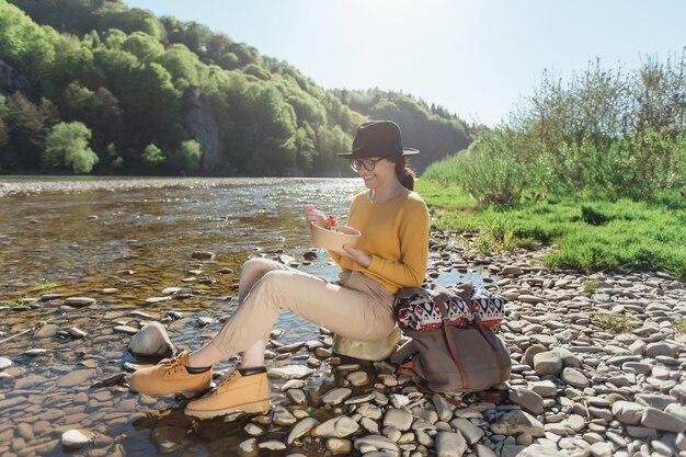 Jonge vrouwenreiziger eet gezond voedsel dichtbij rivier op aardachtergrond