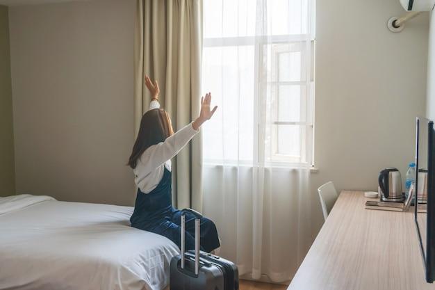 Jonge vrouwenreiziger met bagagezitting op het bed in hotelruimte