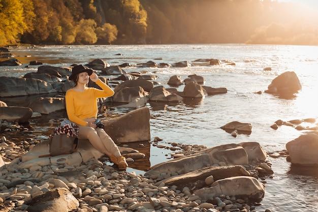 Jonge vrouwenreiziger met celtelefoon in handen die op rots dichtbij riviernatuur zitten