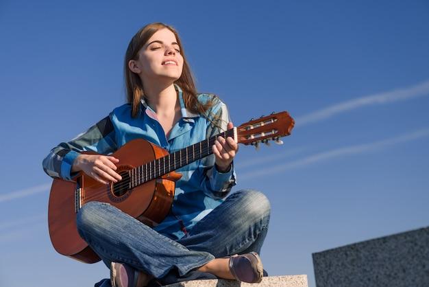 Jonge vrouwenreiziger met gitaar openlucht op overzeese kust