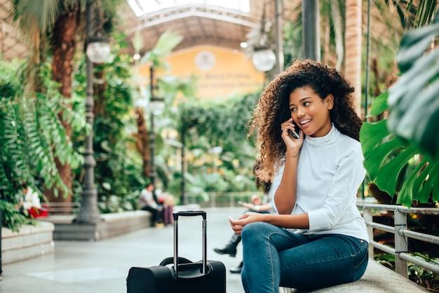 Jonge vrouwenreiziger met haar bagage die op telefoon spreekt.
