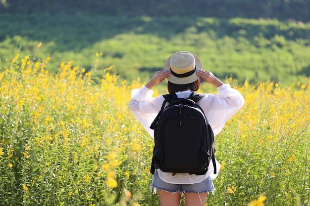 Jonge vrouwenreiziger met rugzak die en op gele bloemen genieten van bevinden zich