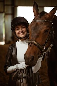 Jonge vrouwenruiter met een bruin mooi paard dat dichtbij in jockeykleren staat selectieve focus een b...