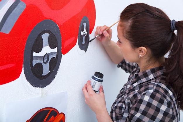 Jonge vrouwenschilder en moederjongen tekent voor een kind op een witte muur een mooie rode auto in een licht