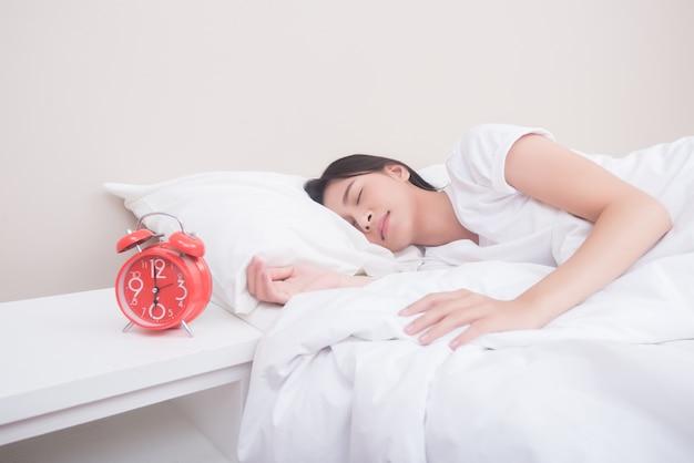 Jonge vrouwenslaap in bed naast wekker