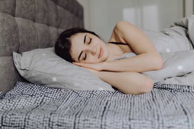 Jonge vrouwenslaap. mooie jonge lachende vrouw slapen in bed